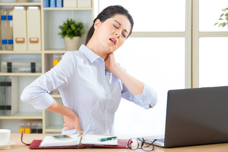 Photo pour Young asian business woman with pain in neck in office - image libre de droit
