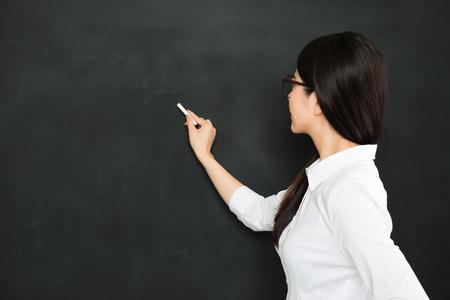 Foto de A good asian teacher writing on blackboard with chalk in classroom - Imagen libre de derechos