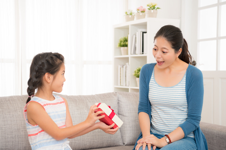 lovely asian little girl send a gift to her beautiful mother at mother\'s day at home in the living room sitting on the sofa together when the holiday resting.