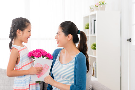 smiling asian little girl prepare a pink carnation bouquet and love card giving gift for beautiful mother at mother's day at home in the living room sofa looking each other with copyspace.