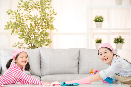 Photo for happy mother with kids spring cleaning room and having fun playing at home. A young woman and a little child girl dusting. family housework and household concept. - Royalty Free Image