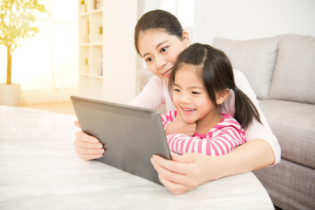 Foto de beautiful young mother and her cute daughter in shirts laughing and looking in digital tablet in the living room at home. family activity concept. - Imagen libre de derechos