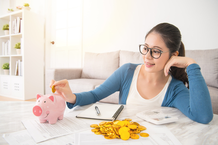 Photo pour young mixed race asian woman deposit gold coin into piggy bank for future life sitting on sofa drinking coffee in the living room at home. interior and domestic housework concept. - image libre de droit