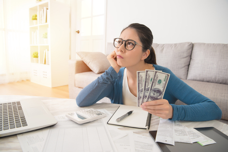 Photo for Attractive young mixed race asian woman working on finances worried about the expend cost sitting on sofa in the living room at home. interior and domestic housework concept. - Royalty Free Image