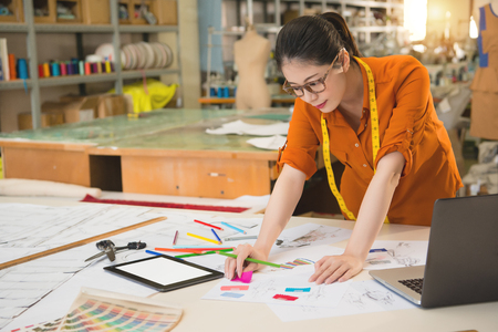 Photo pour Chinese Asian design school  woman has ponytail thinks how to drawing with colorful pencil and ruler and scissors in studio  in manufacturing office studio. profession and job occupation concept - image libre de droit