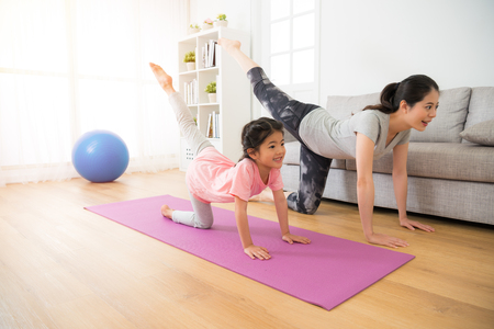 Foto de asian pretty mother and her youth kid daughter in the gym center doing stretching fitness exercise yoga together, parent accompany children sport concept. - Imagen libre de derechos