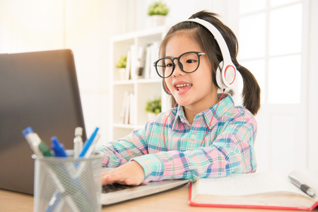 Photo pour e-learning give preschool kids perfect study resource. asia cute sweet children typing with computer keyboard and listen headsets. - image libre de droit