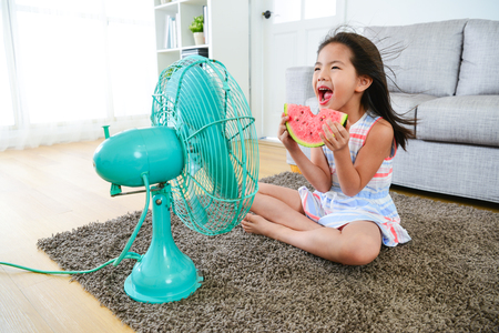 Foto de beautiful youth girl holding watermelon sitting in front of electric fan and blowing cool fan for eliminating summer hot. - Imagen libre de derechos