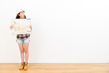 shocked female traveler excitedly looking at copyspace area feeling surprise travel information holding map on white background with wood floor.