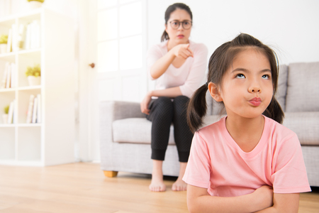 Photo pour young lovely children was bored with her angry mother loudly nag feeling impatient hate annoying when mom was sitting behind her on sofa in living room at home. - image libre de droit