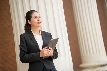 Photo pour beautiful female lawyer holding digital tablet computer standing in front of court through internet to provide customers online consulting services. - image libre de droit
