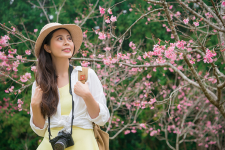 beautiful smiling tourist woman watching cherry blossom flowers at famous sakura trees park and enjoying spring season vacation in japan travel.