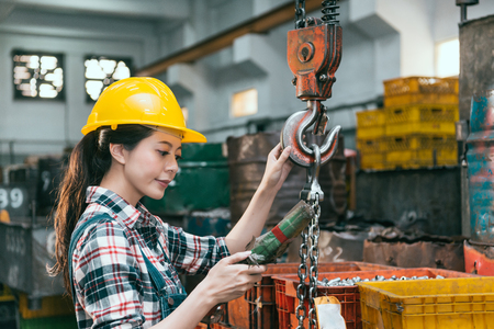 Photo for confident elegant milling machine factory worker wearing helmet and adjusting remote control using chain crane to ship components finished product. - Royalty Free Image