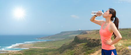 Foto de young athlete jogger on the top of the hill holding the bottle drinking water to add energy after running training physical fitness endurance banner with copy space. - Imagen libre de derechos