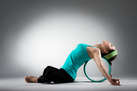 Foto de elegant female gym player lying on pilates ring stretching body meditation workout softness when she sitting in grey wall background. - Imagen libre de derechos