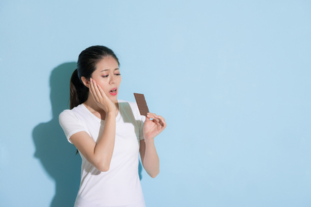 Photo pour beauty young woman looking at chocolate cookie standing on blue wall background and feeling teeth painful because she having tooth decay problem. - image libre de droit