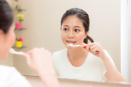Photo pour young smiling housewife using toothbrush cleaning teeth after eating food or waking up in morning standing on bathroom looking mirror brushing. - image libre de droit