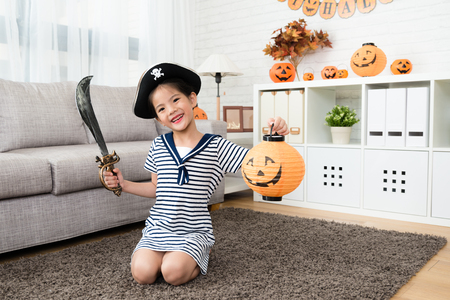Foto de cute girl wear the pirate costume and holding a pumpkin lantern playing Halloween game and sitting on the floor at living room - Imagen libre de derechos