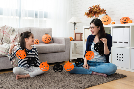 school kid holding the Halloween paper cut decorations with her mother and look at each other sitting in the living room