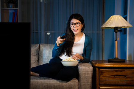 Photo pour happy attractive lady eating popcorn and selection tv channel searching interesting movie sitting on sofa couch in living room at night. - image libre de droit
