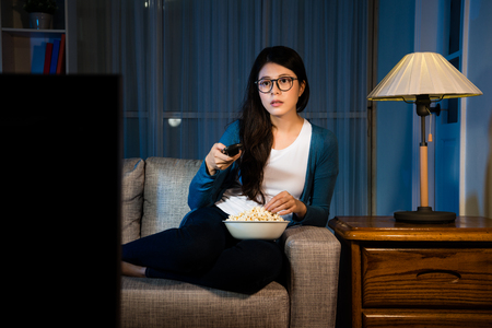 Foto de pretty sweet female student holding remote control looking at television and eating delicious popcorn snack at night in living room comfortable sofa. - Imagen libre de derechos