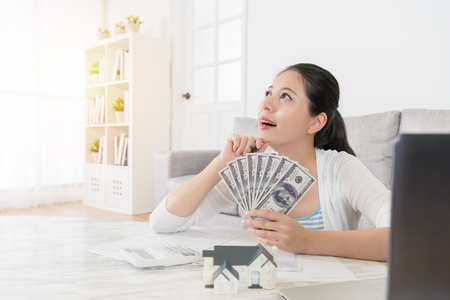 Foto de happy young housewife counting personal saving money banknote in living room and daydreaming thinking how to invest new estate - Imagen libre de derechos