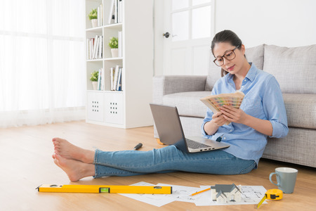 Foto de happy attractive woman sitting on living room floor using mobile laptop design new house and holding palette chart tool choosing color. - Imagen libre de derechos
