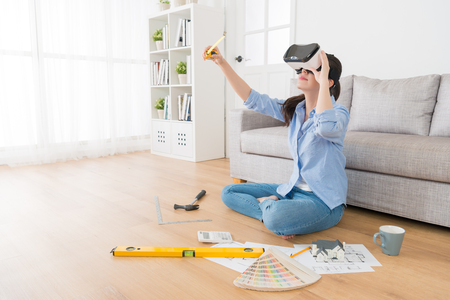 Photo pour professional young woman designer wearing VR glasses looking 3D simulation video and using measuring tape checking design. - image libre de droit