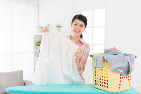Photo pour smiling attractive woman holding white shirt checking clean and looking at camera when she folding clothing at home in living room. - image libre de droit