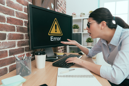 Photo pour sadness suit woman sitting on working desk using keyboard typing making report but computer showing error information let her feeling dumbfounded. - image libre de droit