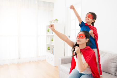 Foto de happy mother with little daughter on living room sofa play as superhero together and making same posing ready to fly at holiday leisurely time. - Imagen libre de derechos