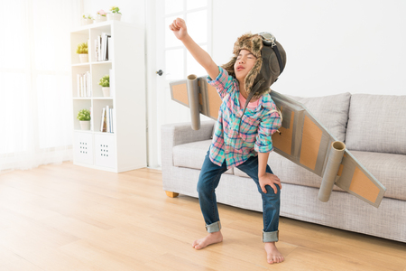 Foto de beautiful young little girl children standing on living room floor showing fly posing and wearing wings decoration play as astronaut. - Imagen libre de derechos