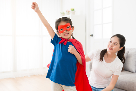 Foto de happy lovely little girl wearing superhero clothing making ready to fly posing and looking at camera smiling in living room with beautiful young mother. - Imagen libre de derechos