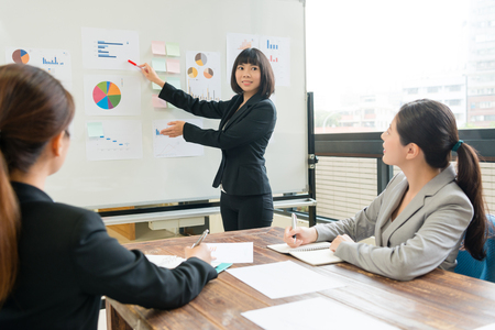 Foto de young beautiful business woman presenting new corporation case plan for all partner on whiteboard during company meeting. - Imagen libre de derechos
