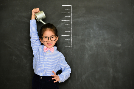 Photo pour confidence happy girl kid face to camera smiling and irrigating body measured growth height isolated on black chalkboard background. - image libre de droit