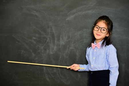 Photo pour smiling pretty little teacher using stick pointing chalkboard empty screen showing school studying concept standing in blackboard background. - image libre de droit