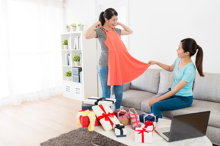 Foto de beautiful woman holding new summer dress let her sister looking and check whether suitable and using mobile computer online shopping at home. - Imagen libre de derechos