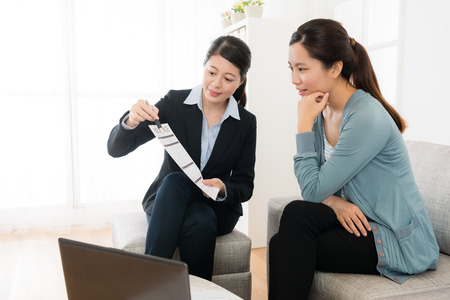 Photo pour friendly pretty business worker woman holding document showing insurance plan for young investor and explaining best price. - image libre de droit
