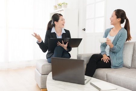 Photo pour happy attractive lady sitting on sofa at home talking with her insurance advisor and discussing plan reached consensus feeling cheerful. - image libre de droit