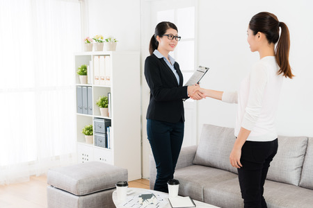 Foto de happy friendly business lady with her client handshake when they finished house deal and looking each other talking together. - Imagen libre de derechos