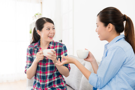Photo pour cheerful pretty sisters sitting on sofa couch chatting and drinking hot coffee relaxing during holiday at home in living room. - image libre de droit