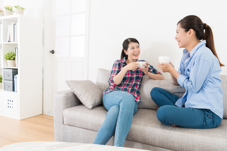 Foto de happy pretty woman talking with her best sister and enjoying tea time together during leisurely holiday in living room at home. - Imagen libre de derechos