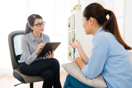 Photo pour beautiful young female psychologist doctor using mobile digital tablet recording all information from her patient talking. - image libre de droit