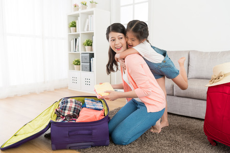 Photo pour Happy girl hugging beautiful mother in living room feeling cheerful when woman packing luggage suitcase at home ready to travel. - image libre de droit