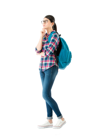 Foto de young pretty woman carrying school backpack standing on white wall background and thinking about education study problem solution. - Imagen libre de derechos