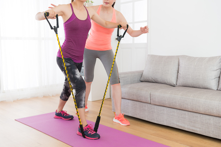 Photo pour powerful attractive female fitness girl using resistance band training body with her workout teacher at home. - image libre de droit