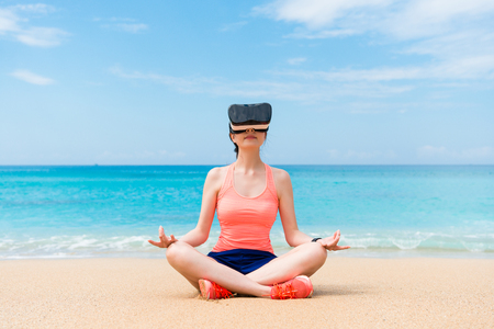 smiling beautiful fitness sporty girl wearing VR device sitting on beach and looking at 3D zen video to workout with lotus posture.