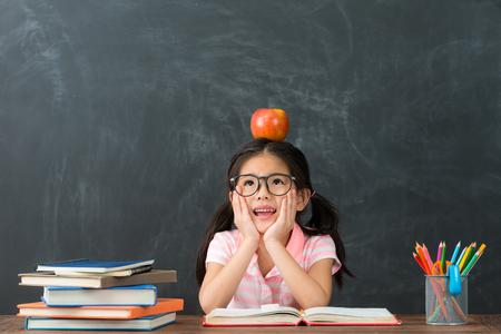 Foto de beautiful pretty female kid student studying in blackboard background and daydreaming prepare back to school. - Imagen libre de derechos