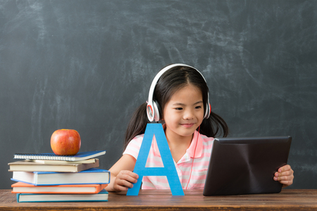 Foto de smiling young female kid children using digital tablet pad watching online e-learning video to studying english in chalkboard background. - Imagen libre de derechos