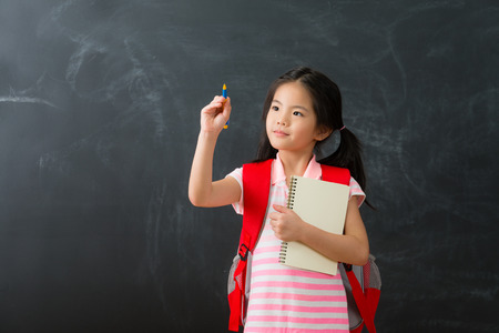 smiling pretty little girl children using pen writing note on simulation screen and carrying studying tool with bag back to school learning isolated on blackboard background.